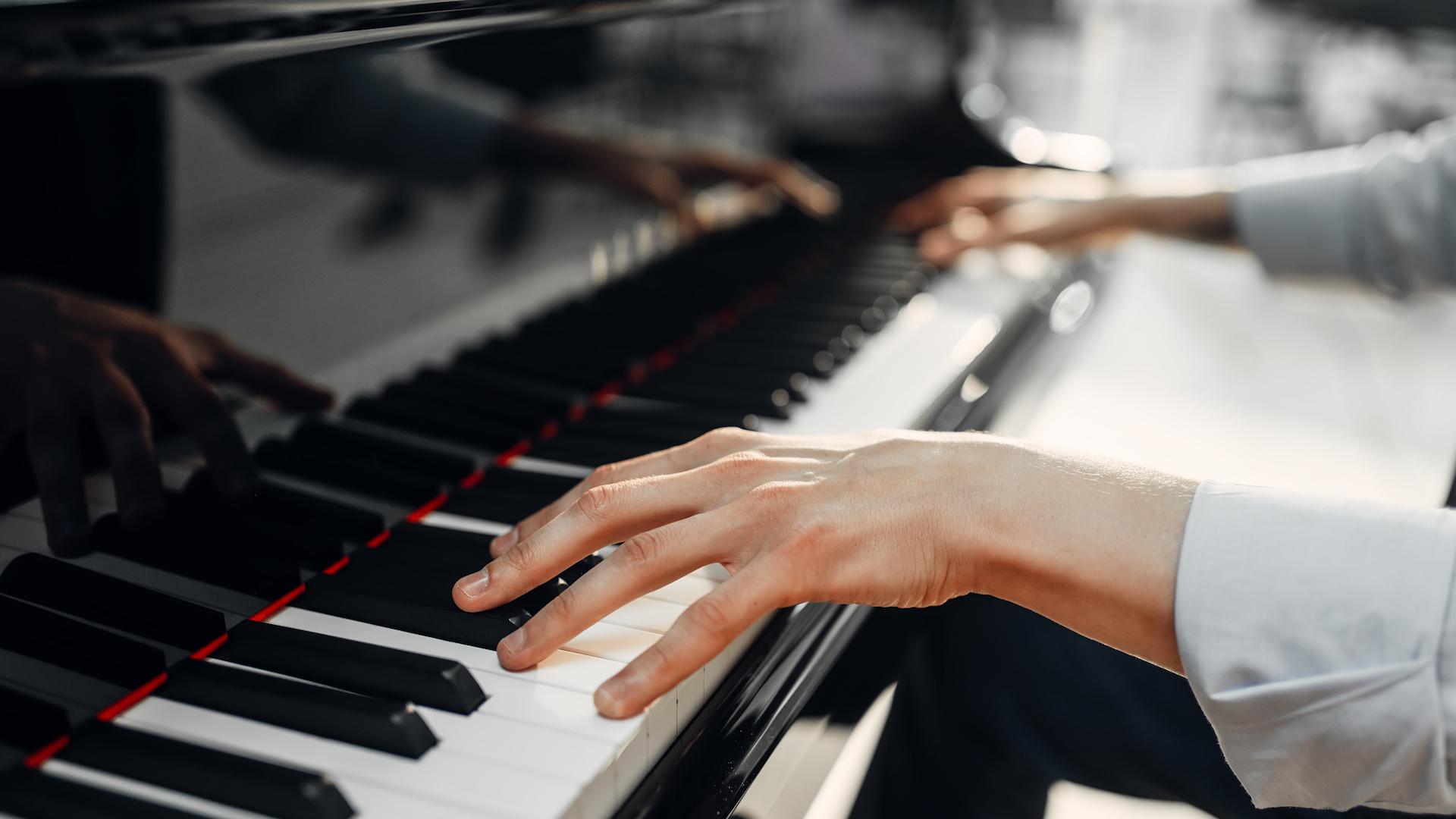 Plano detalle de las manos de un pianista interpretando una pieza musical