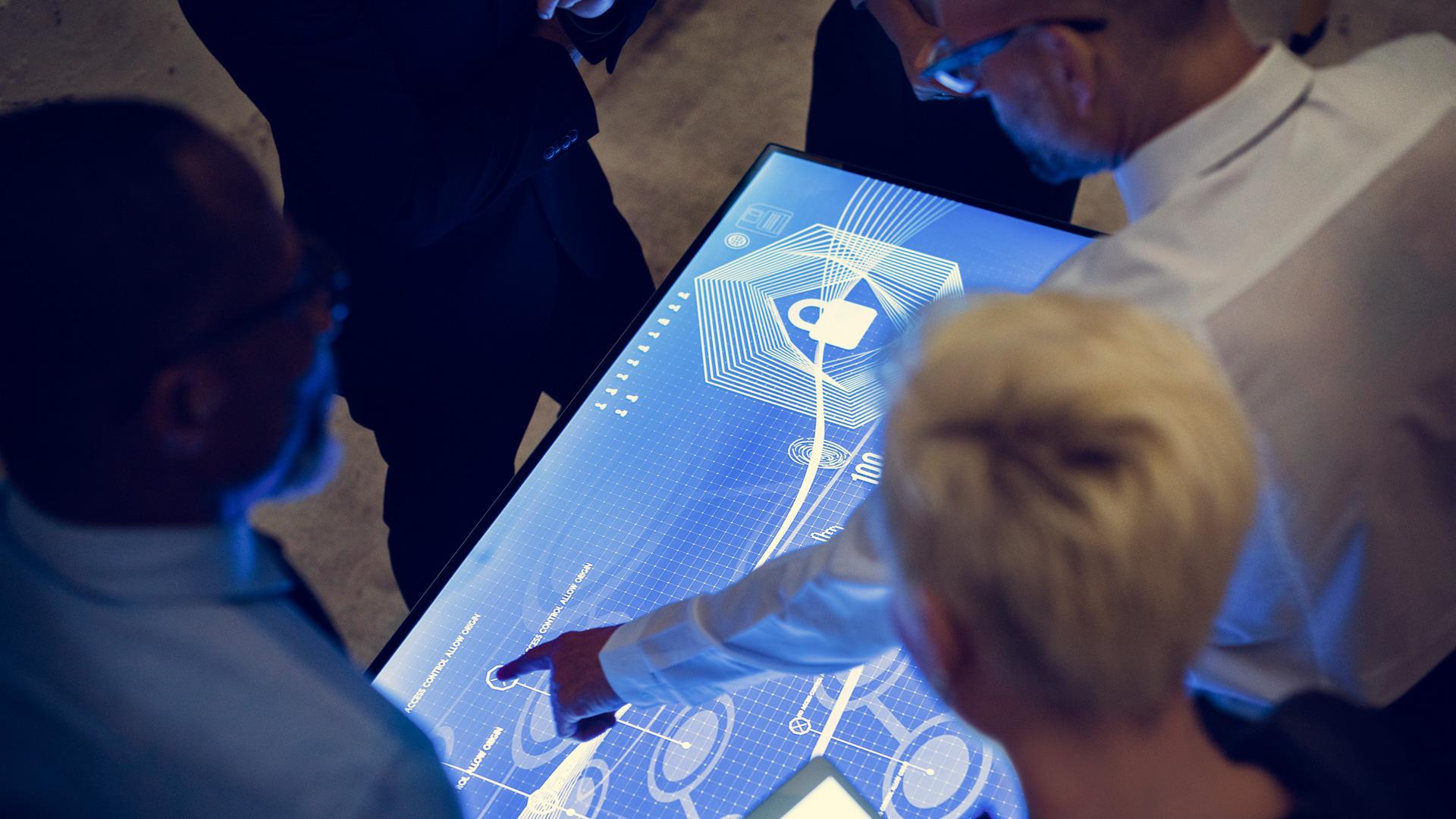 Personas alrededor de una pantalla táctil, con un hombre dirigiendo la reunión y controlándola