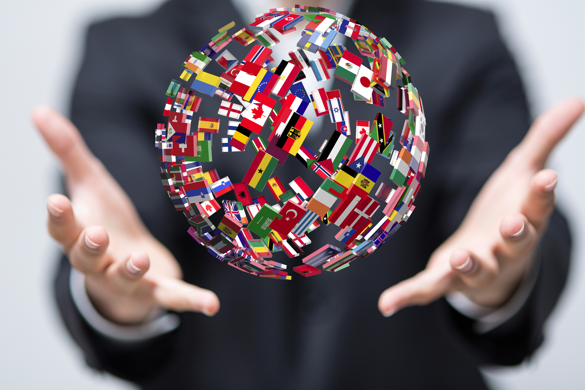 Manos de una persona con una bola del mundo con banderas de todos los paises. Comercio Internacional.