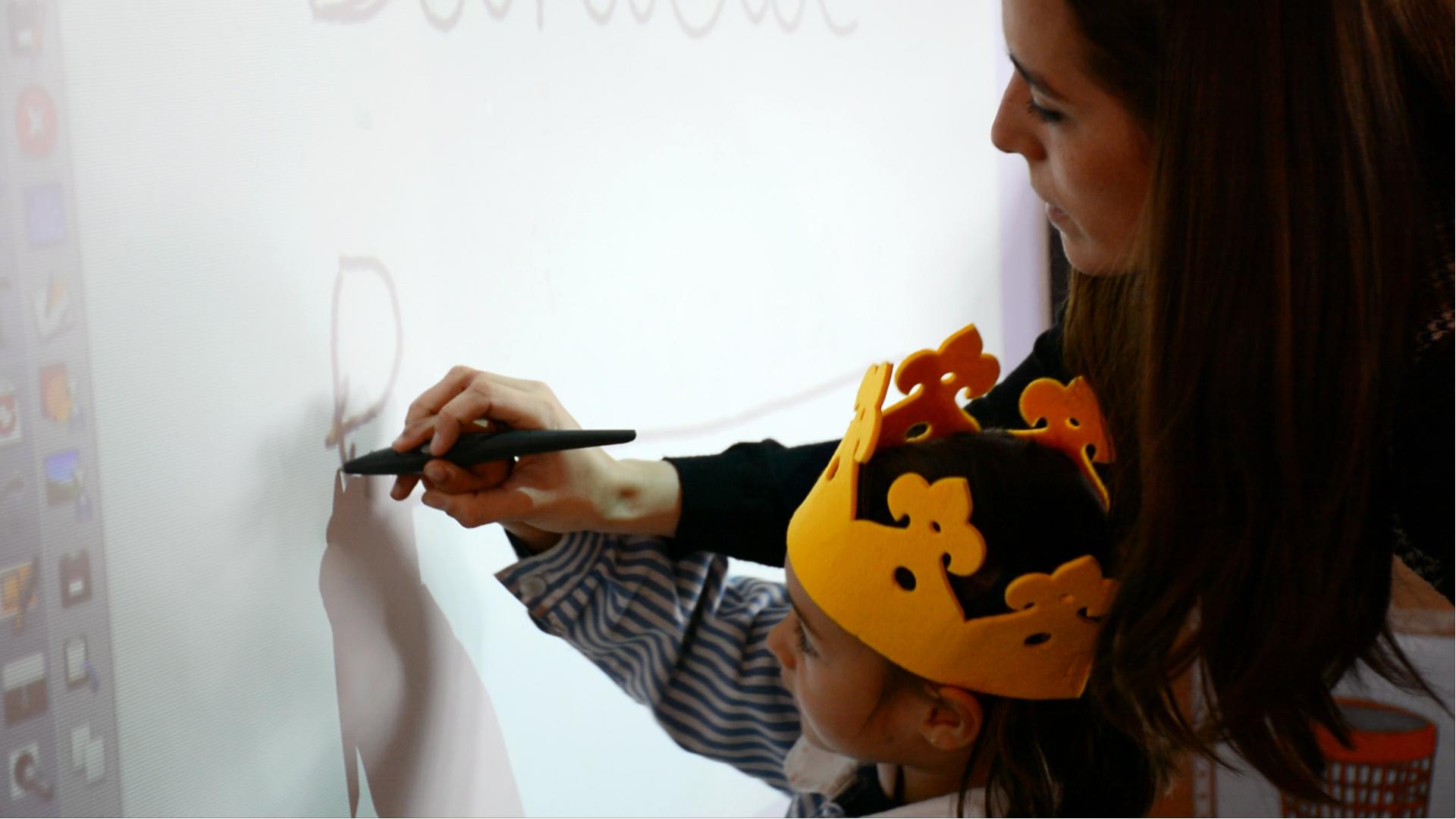 Profesora de educación infantil enseñando a un alumno a dibujar en la pizarra digital