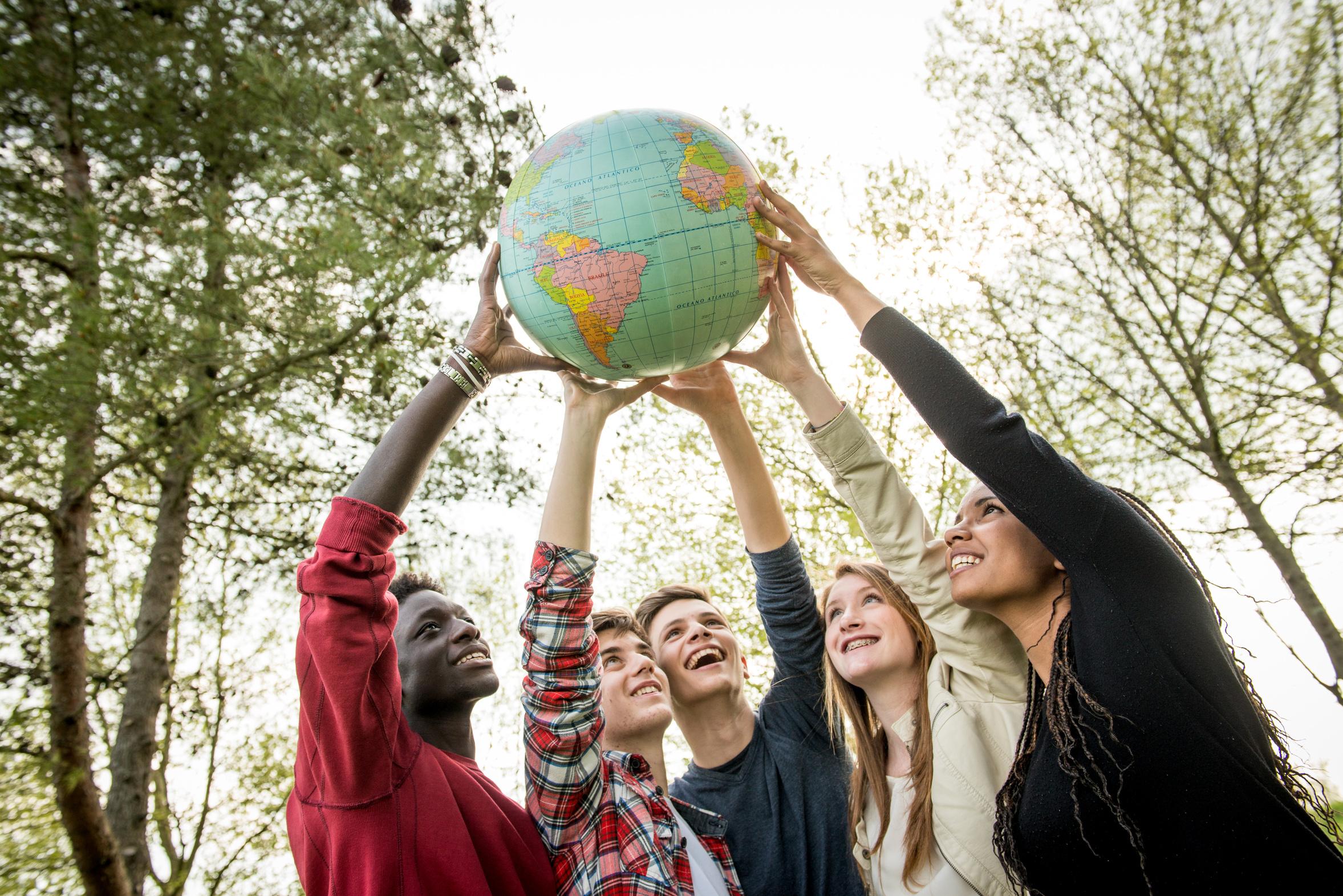 Imagen de bola del mundo cogida por las manos de jóvenes que reflejan la integración social