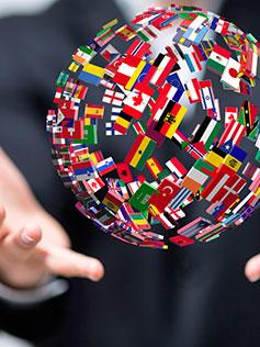 Manos sosteniendo bola del mundo con las diferentes banderas de los paises
