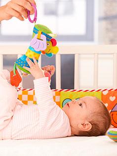 Bebe en una cuna entretenido con un juguete que sostiene la madre