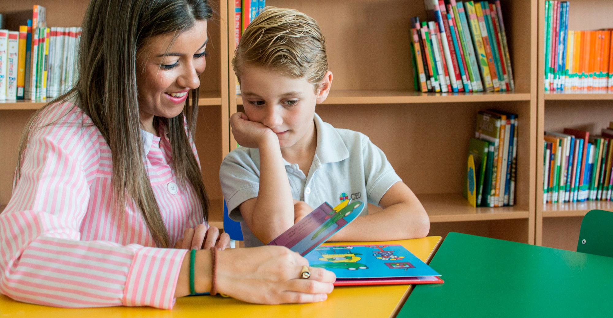 Maestra del Grado de Educación Infantil enseñando a un alumno
