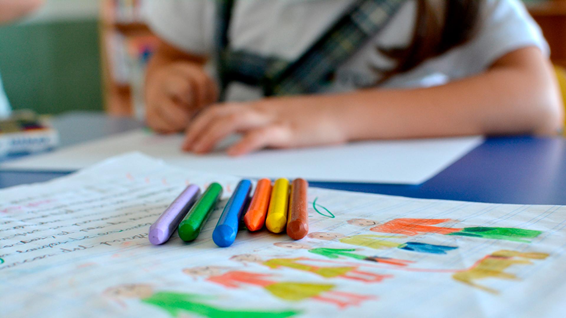 Estudiante del FP de educación infantil enseñando a un alumno a pintar en la pizarra digital