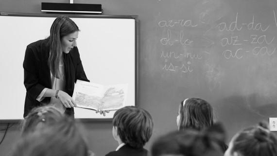 Maestra de educación infantil enseñando a un alumno en una clase